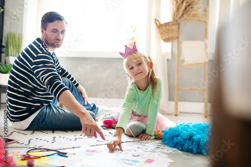 Valokuva  Cute girl feeling involved in studying with daddy