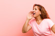 canvas print picture middle age woman profile view, looking happy and excited, shouting and calling to copy space on the side against pink wall