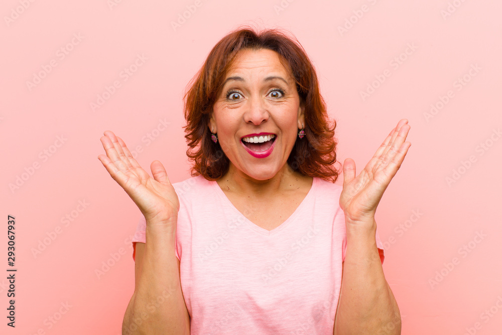 Fototapety, obrazy: middle age woman looking happy and excited, shocked with an unexpected surprise with both hands open next to face against pink wall