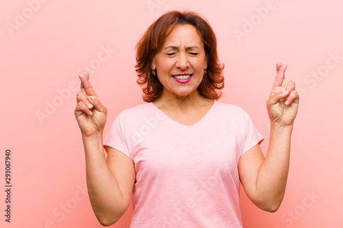 middle age woman smiling and anxiously crossing both fingers, feeling worried an Fototapet