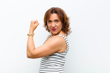 Middle Age Pretty Woman Feeling Happy, Satisfied And Powerful, Flexing Fit And Muscular Biceps, Looking Strong After The Gym Against White Wall