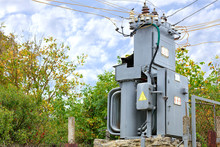 Transformer Substation Stands In The Middle Of The Garden Against A Blue Cloudy Sky.