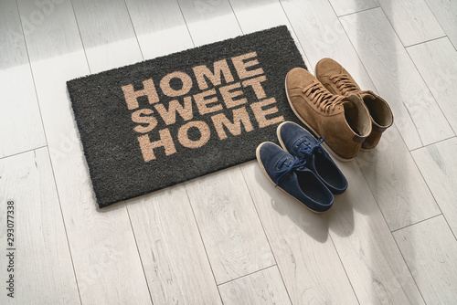 Photographie Home sweet home doormat at condo door entrance with couples pairs of shoes moving in together