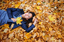 Woman Lying With Autumn Leaves In City Park, Outdoor Portrait