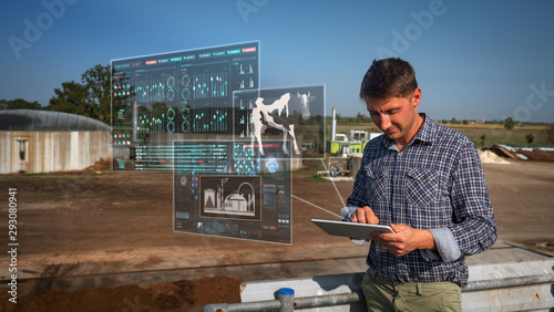 An young agronomist is using a tablet with futuristic augmented reality holograms for controlling a quality of an organic cow manure compost used for agricultural soil cultivation and for biogas Canvas Print