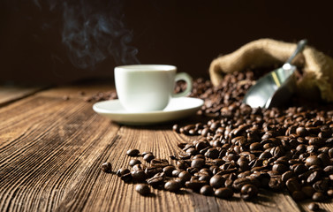 Cup of espresso with coffee beans, bag, scoop and steam