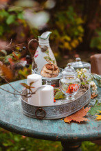 Cozy Patio. Autumn Leaves Lie On A Wooden Antique Round Table With Crockery Cups And Cookies And Candles.