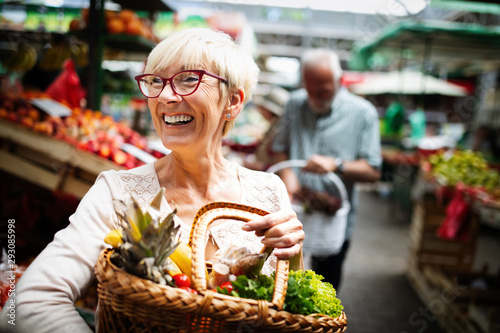 Mature woman buying vegetables at farmers market Canvas-taulu