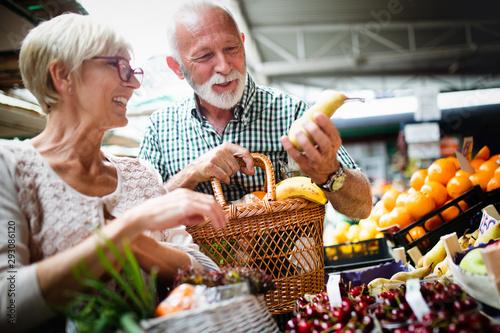 Portrait of beautiful elderly couple in market buing food - 293086120