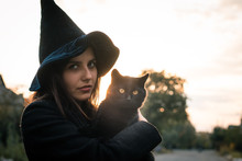 Halloween Cat In Hands And A Witch Girl Wearing A Black Hat And Coat On An Autumn Sunset. Celebration And Pets Concept.