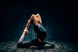Young woman practicing yoga doing one legged king pigeon pose in dark room