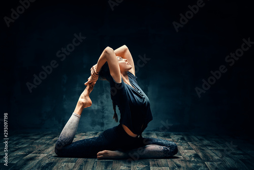 Young woman practicing yoga doing one legged king pigeon pose in dark room Wallpaper Mural