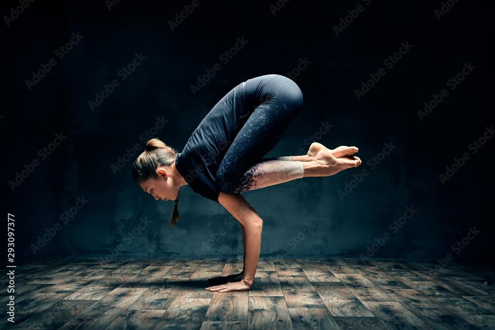 Fototapeta Young woman practicing yoga doing forearm stand crane pose asana in dark room