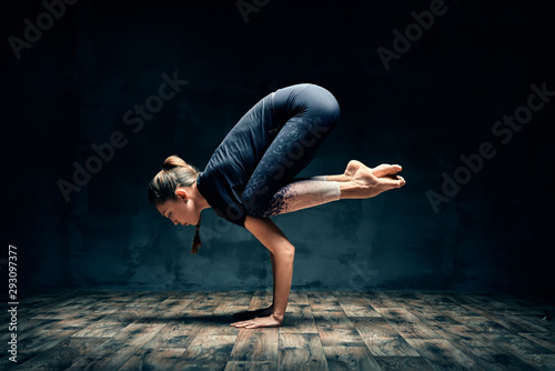 Stampa su Tela Young woman practicing yoga doing forearm stand crane pose asana in dark room
