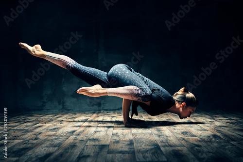 Pinturas sobre lienzo  Young woman practicing yoga doing hurdler pose in dark room