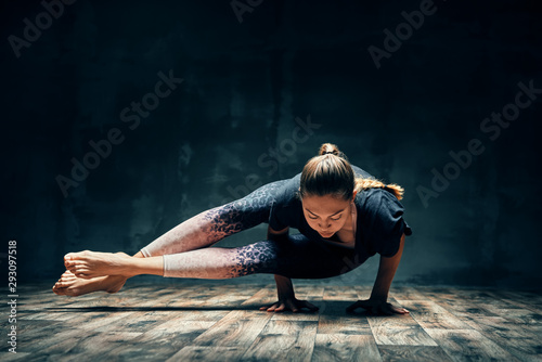 Young woman practicing yoga doing eight-angle pose asana in dark room