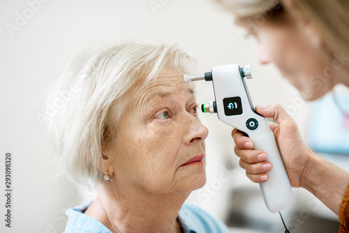 Obraz Female ophthalmologist measuring the eye pressure with modern tonometer to a senior patient in the medical office, close-up view - fototapety do salonu