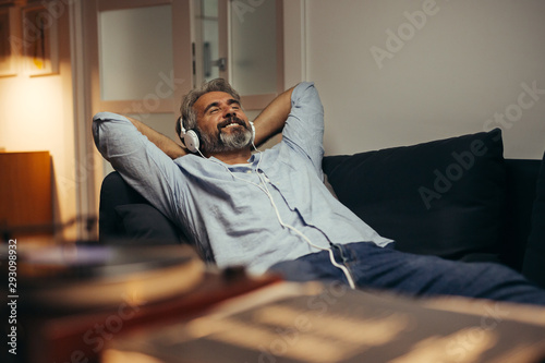 middle aged man listening music at his home - 293098932