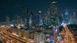 Skyscrapers aerial paniramic view in downtown and financial district Dubai at night, traffic on highways. United Arab Emirates with illuminated towers