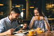 happy young couple eating in restaurant