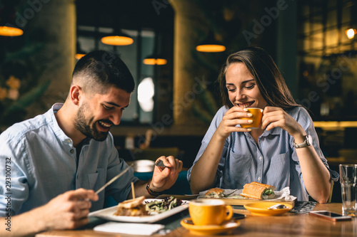 happy young couple eating in restaurant Canvas Print