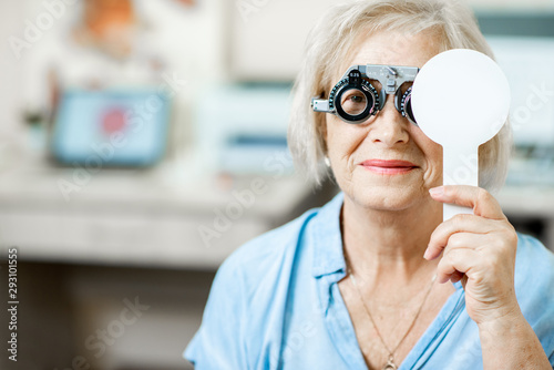 Fotografía Senior woman checking vision with eye test glasses and scapula during a medical