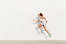 Image Of Redhead Young Woman Running Along White Wall While Doing Workout In Morning