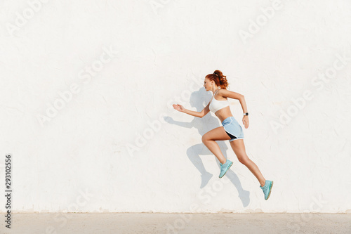 Fotografia Image of redhead young woman running along white wall while doing workout in mor