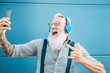 Leinwanddruck Bild - Senior crazy man taking self video while listening music with headphones - Hipster guy having fun using mobile smartphone playlist apps - Happiness, technology and elderly lifestyle people concept