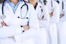 Group Of Modern Doctors Standing As A Team With Arms Crossed In Hospital Office. Physicians Ready To Examine And Help Patients. Medical Help, Insurance In Health Care, Best Desease Treatment And