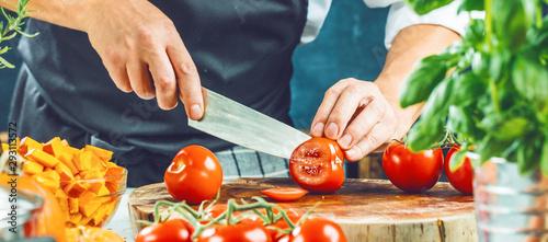 Obraz na płótnie Koch schneidet frische rote Tomaten in Restaurant küche