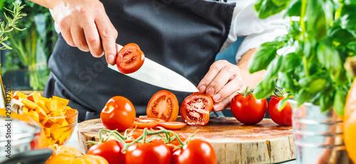 Tela Koch schneidet frische rote Tomaten in Restaurant küche