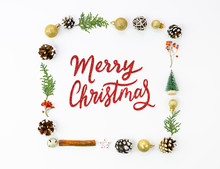 Merry Christmas Red Sparkles Lettering Sign Framed By Xmas Decorations, Golden Balls, Pinecones Isolated On White
