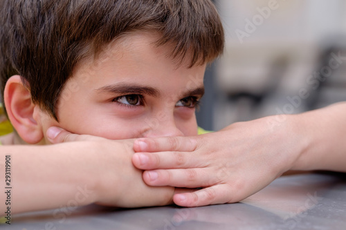Photo Niño se tapa la boca con las manos y la cabeza apoyada en una mesa