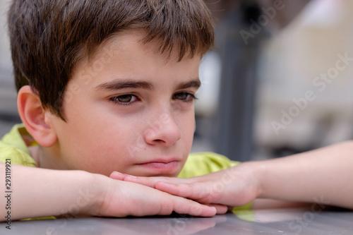 Niño aburrido con las manos y la cabeza apoyada en una mesa Canvas Print