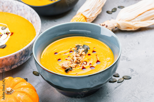 close-up view of pumpkin soup puree in bowls, corn and pumpkins on table