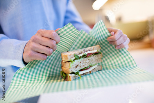Photo Close Up Of Woman Wrapping Sandwich In Reusable Environmentally Friendly Beeswax