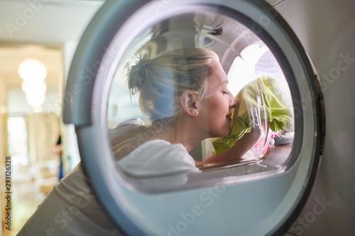 Hausfrau mit frischer Wäsche in der Waschmaschine Canvas Print