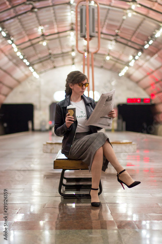 Photo  Business woman with a cup of coffee is reading a newspaper
