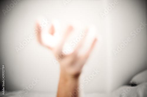 unscharfe Hand vor weißer Wand vor Bett in Positionierung Canvas Print