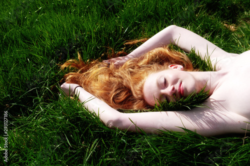 Photo Beautiful Portrait of a young sexy red-haired woman, raising her arms, lying in the summer sun on the green grass, the red hair draped freely around the head