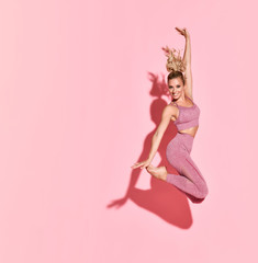 Happy athletic woman jumping in silhouette. Photo of sporty woman in fashionable pink sportswear on pink