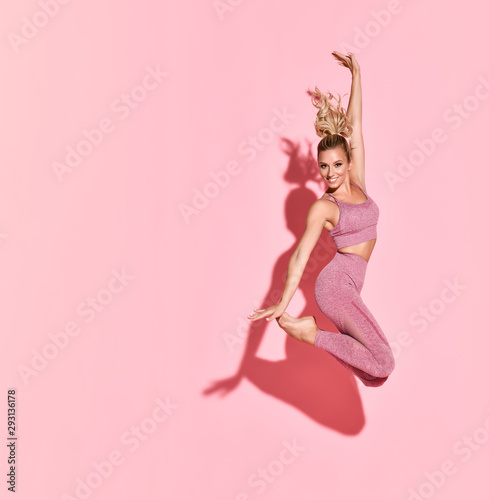 fototapeta na lodówkę Happy athletic woman jumping in silhouette. Photo of sporty woman in fashionable pink sportswear on pink