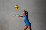 Young Asian woman volleyball player in blue uniform with ball