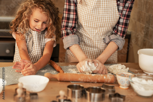 Obraz Mother and daughter playing and preparing dough in the kitchen. - fototapety do salonu