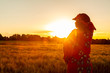 canvas print picture - African woman in traditional clothes standing in a field of crops at sunset or sunrise