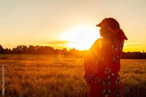 Fototapeta African woman in traditional clothes standing in a field of crops at sunset or sunrise obraz