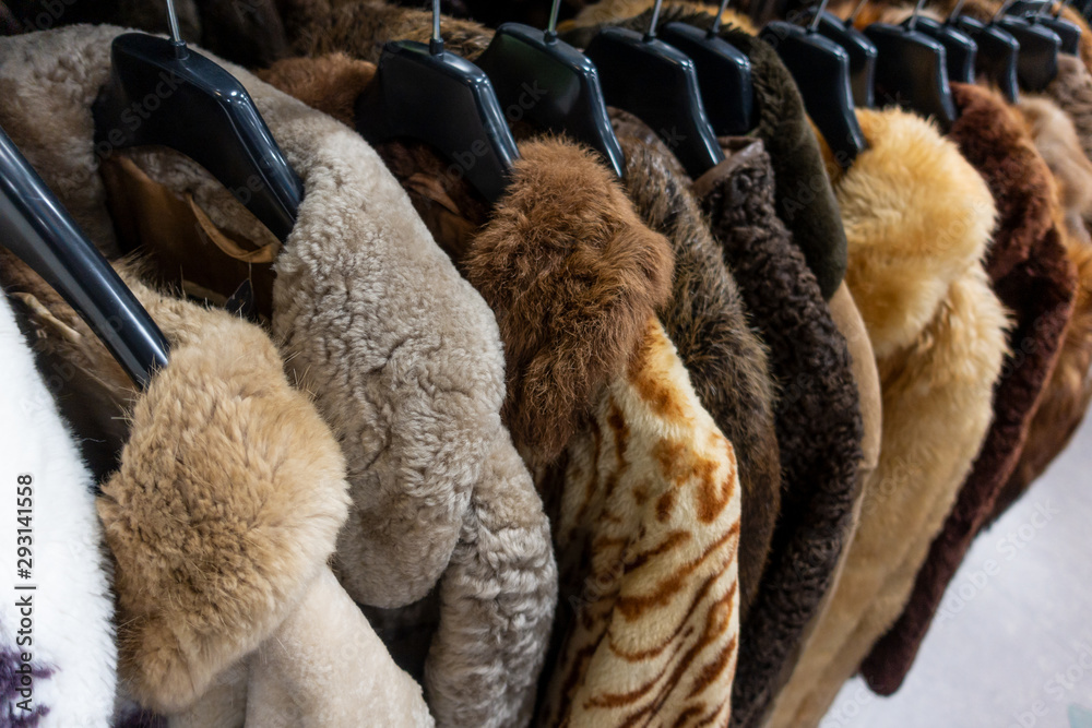 Fototapeta Rail of Secondhand Fur Coats For Sale in a Thrift Store Shop