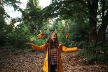 Happy Smiling Young Woman Throwing Autumn Leaves In The Air In The Forest
