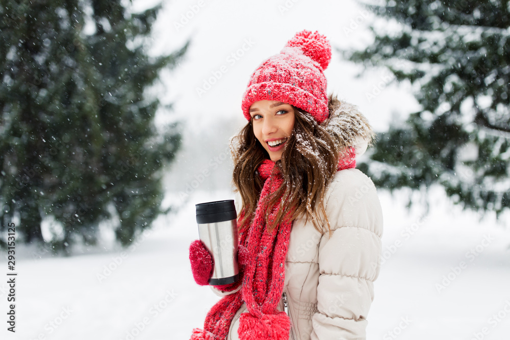 Fototapeta people, season, drinks and christmas concept - happy teenage girl or young woman with hot drink in tumbler outdoors in winter park